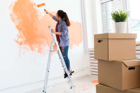 Smiling woman painting interior wall of home. Renovation, repair and redecoration concept.