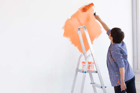 Happy middle-aged woman painting interior wall with paint roller in new house. A woman with roller applying paint on a wall. Copy space.