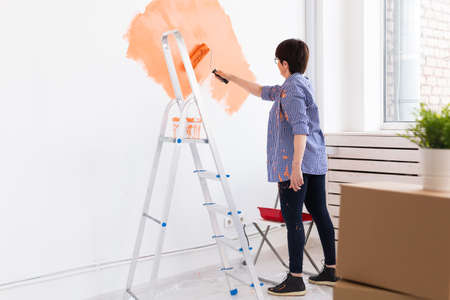 Happy middle-aged woman painting wall in her new apartment. Renovation, redecoration and repair concept. Stockfoto