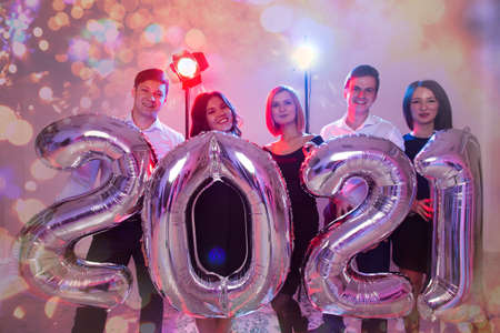 Party, people and new year holidays concept - women and men celebrating new years eve 2021