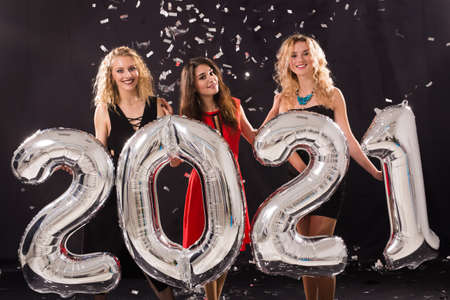 Party, people and new year holidays concept - cheerful young women celebrating new years eve 2021