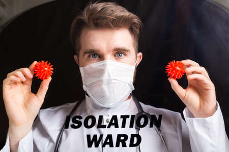 Covid-19 ward, Vaccine development and medicine concept - Doctor in flu mask holding a model of coronavirus. 版權商用圖片 - 155264336
