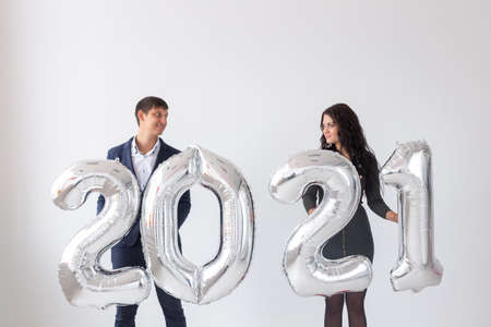 New year, celebration and holidays concept - love couple having fun with sign 2021 made of silver balloons for new year on white background