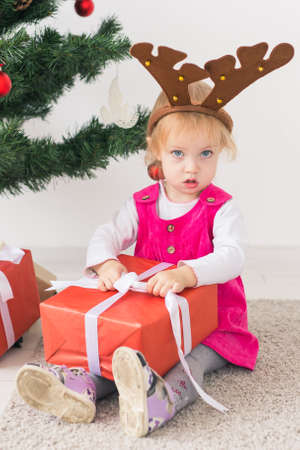 Baby holding Christmas gift. Winter holidays concept.