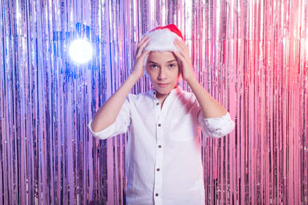 Christmas time. Teen boy with Santa Claus Hat over shiny festive background. Christmas holidays concept.
