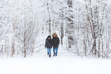 Happy loving couple having fun outdoors in snow park. Winter vacation