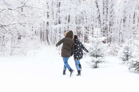 Happy couple walking through a snowy forest in winter 版權商用圖片 - 155185593