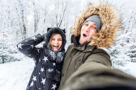 Season and relationship concept - Funny couple taking selfie in the winter time.