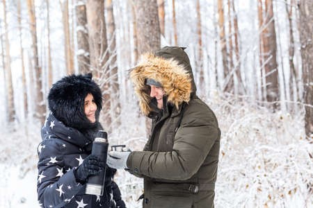 Young couple in love drink a hot drink from a  and enjoy winter nature.