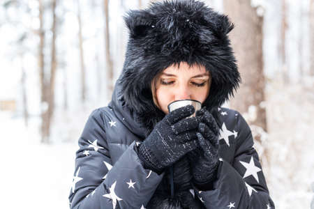 Girl drink a hot drink from a  and enjoy winter nature. 版權商用圖片