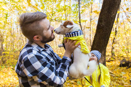 Man with his dog at autumn park. Guy playing with jack russell terrier outdoors. Pet and people concept. 版權商用圖片