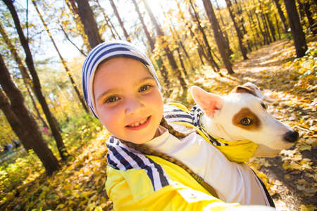 Little girl taking selfie with her dog at autumn park. Child posing with jack russell terrier for a picture on the mobile phone outdoors. Pet and children concept.