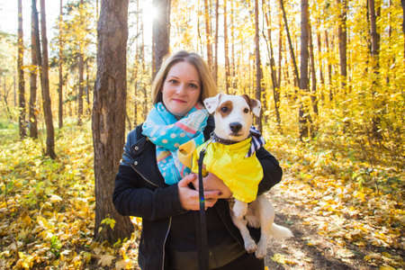 Woman with her dog at autumn park. Girl playing with jack russell terrier outdoors. Pet and people concept. 版權商用圖片 - 155264434