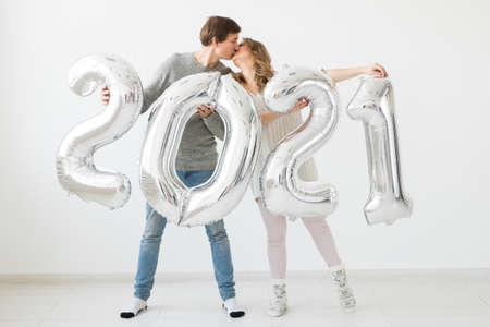 Holidays, festive and party concept - Happy loving couple holds silver 2021 balloons on white background. New Year celebration. 版權商用圖片