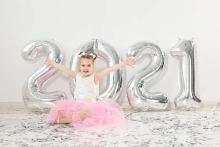 New year, holidays and celebration concept - Little child girl sitting near with numbers balloons 2021