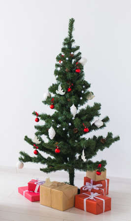 Holidays, celebration and home concept - christmas tree and presents.