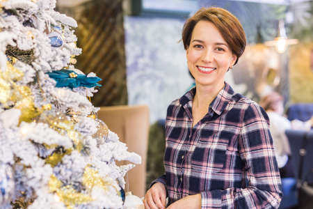 Portrait of happy young woman near christmas tree. Holidays concept.