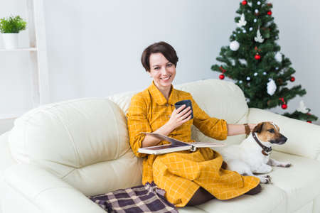 Woman reads book in front of Christmas tree with dog jack russell terrier. Christmas, holidays and pet.