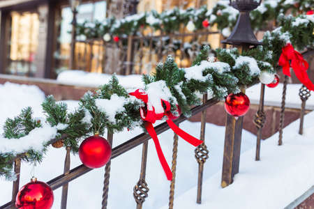 Christmas cityscape - decorating railing porch on the eve of the holiday. Christmas baubles and tapes. Winter holidays.