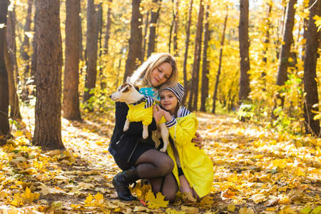 Woman with her dog at autumn park. Girl playing with jack russell terrier outdoors. Pet and people concept.