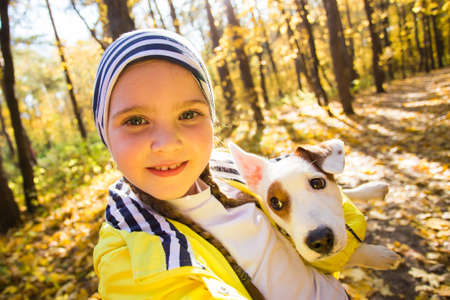 Child taking selfie with dog jack russell terrier. Autumn walk with a dog, children and pet concept. 版權商用圖片