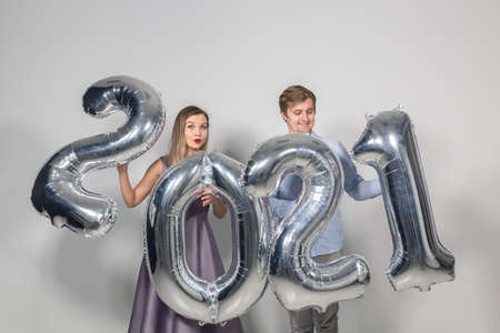 Party, people and new year holidays concept - woman and man celebrating new years eve 2021 版權商用圖片