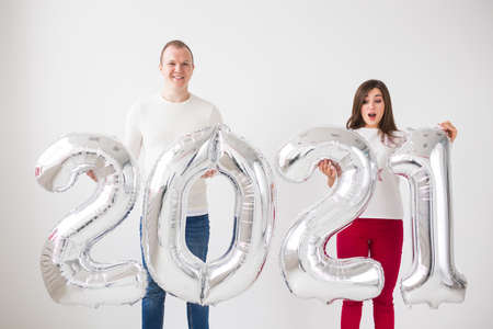 New 2021 Year is coming concept - Happy young man and woman are holding silver colored numbers indoors.