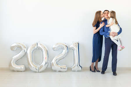Young happy family mother and father and daughter standing near balloons shaped like numbers 2021 on white background. New year, Christmas, holiday