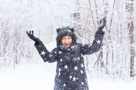 Happy young girl throw up a snow in a winter forest