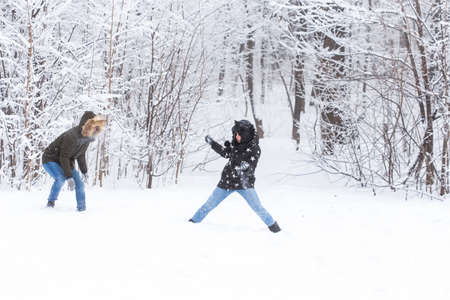 Fun, season and leisure concept - love couple plays winter wood on snow