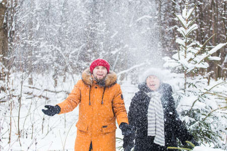 Love, season, friendship and people concept - happy young man and woman having fun and playing with snow in winter forest 版權商用圖片