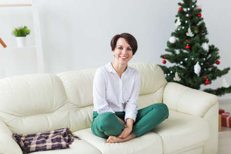 Happy woman on sofa. Christmas tree with presents under it. Decorated living room