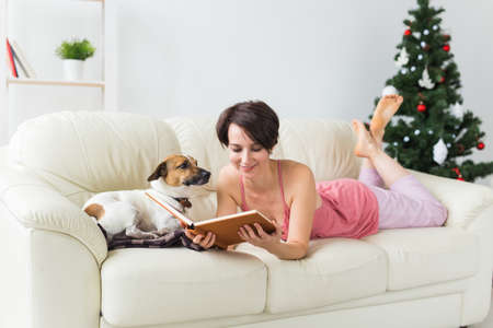Christmas, holidays and people concept - happy young woman reading book at home.