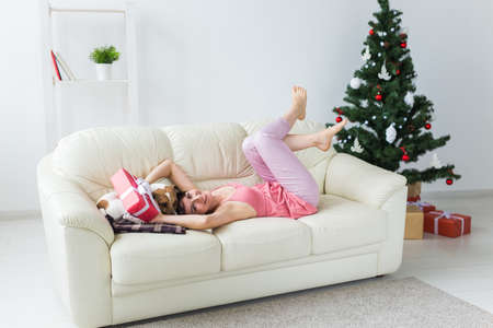 Happy woman with dog. Christmas tree with presents under it. Decorated living room