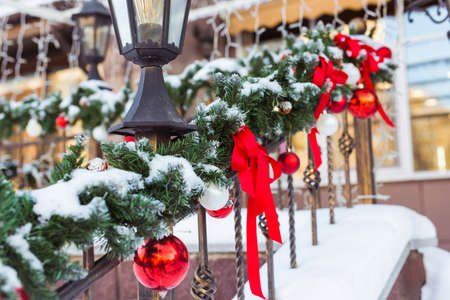 Christmas cityscape - decorating railing porch on the eve of the holiday. Christmas baubles and tapes. Winter holidays. Archivio Fotografico