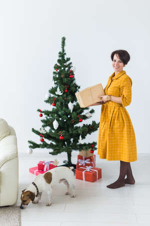 Happy young woman with lovely dog opening present box under christmas tree. Holidays concept. 版權商用圖片