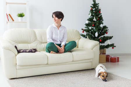 Happy young woman with lovely dog in living room with christmas tree. Holidays concept.