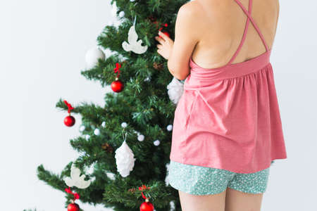 Close-up back view of woman decorating a Christmas tree. Holidays and celebrations concept. 版權商用圖片