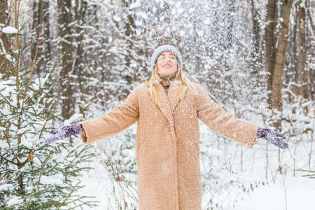 Woman throws up snow, fun and winter concept.