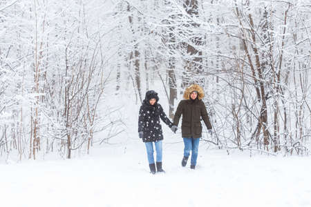 Young couple walking in a snowy park. Winter season.