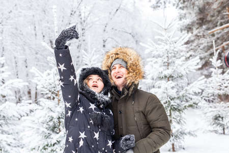 Technologies and relationship concept - Happy smiling couple taking a selfie in a winter forest outside