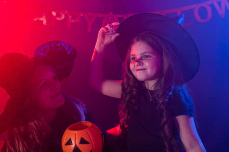 Funny child girl and woman in witches costumes for Halloween with pumpkin Jack. 版權商用圖片