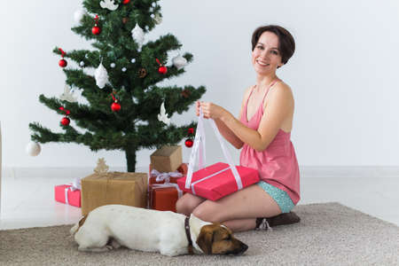 Happy woman with dog opening Christmas gifts. Christmas tree with presents under it. Decorated living room