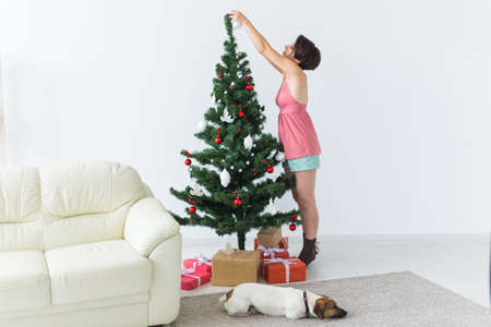 Beautiful young woman decorating a Christmas tree. Holidays and celebrations concept. 版權商用圖片