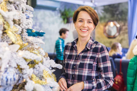 Portrait of smiling young woman near christmas tree. Holidays concept.