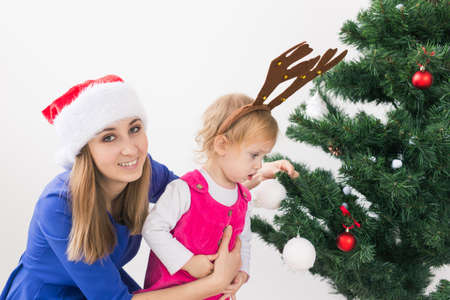 Christmas concept - mother and her little daughter with Christmas tree at living room 版權商用圖片