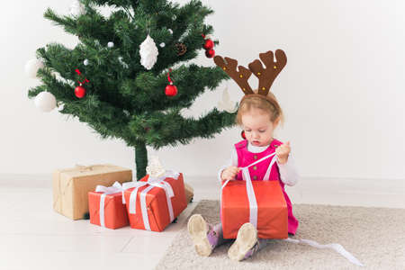 Child holding Christmas gift. Kid having fun at home. Xmas winter holiday concept