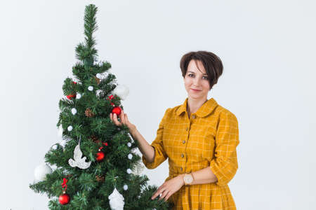Portrait of smiling young woman decorating christmas tree. Holidays concept.