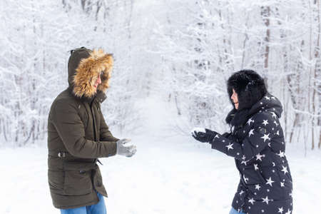 Fun, season and leisure concept - love couple plays winter wood on snow. Foto de archivo
