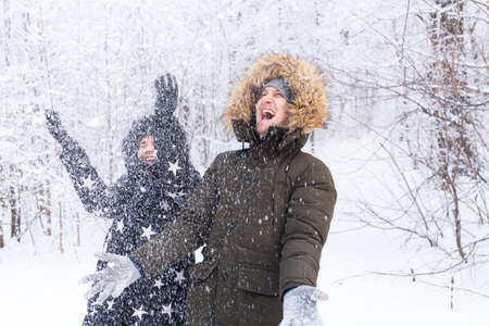 Happy young couple throw up a snow in a winter forest